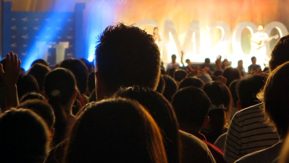 A crowd of people looking at an illuminated stage